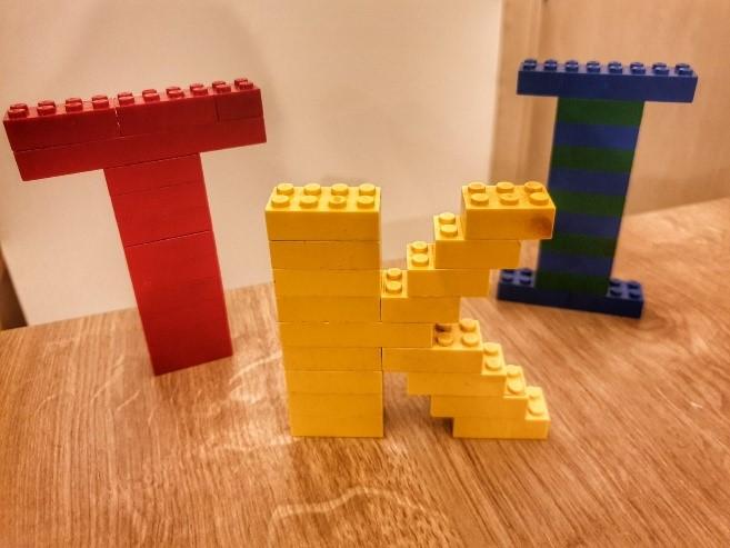 Slika na kojoj se prikazuje stol, igračka, sjedenje, drveni  Opis je automatski generiran